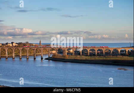 A Virgin Trains East Coast Intercity 225 electric train crosses the Royal border bridge at  Berwick upon Tweed with - Stock Photo