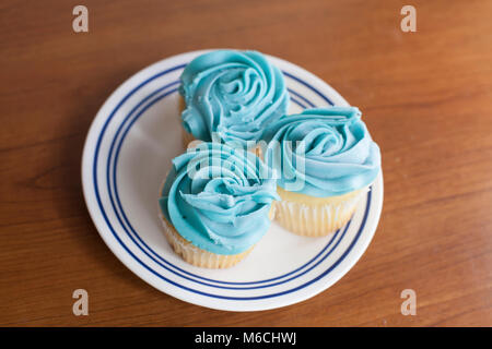 Trio of vanilla cupcakes with blue icing on a plate - Stock Photo