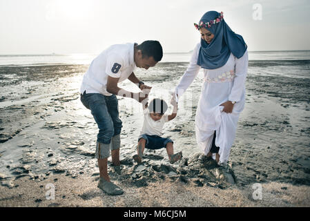 happy asian family wearing casual and playing with mud at the muddy beach located in pantai remis, kuala selangor, - Stock Photo