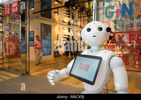 A robot welcomes shoppers to the flagship Uniqlo store in Ginza, Tokyo, Japan - Stock Photo