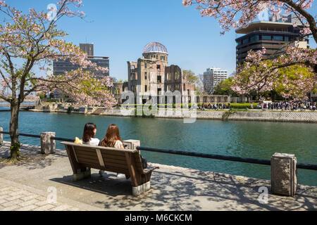 Ota River, with Hiroshima Atomic Bomb Dome, Peace Memorial Park, Hiroshima, Japan and tourists - Stock Photo