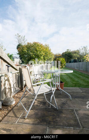 a typically british suburban garden with a patio, lawn, table and chairs - Stock Photo