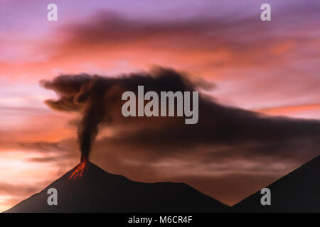 Lava flows down slopes as dark smoke and ash mingle with blur of clouds against sunset hues as Fuego volcano in - Stock Photo