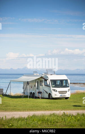 Motorhome parking nearby the water at Engeloya, Norway. The wall of Lofoten Oslands is rising in the horizon. - Stock Photo