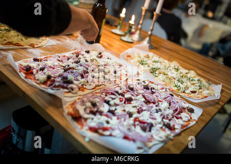 Female hand is topping a home made pizza with grated parmesan cheese. - Stock Photo