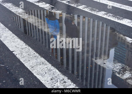 Reflection of the General Motors building in a puddle on New York's Fifth Avenue - Stock Photo