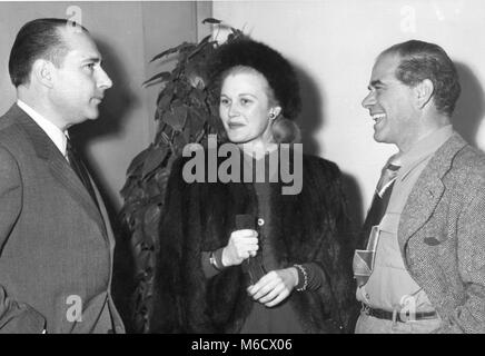 Roberto Rossellini (left), famous Italian motion picture director, talks with film actress Joan Caulfield and film - Stock Photo