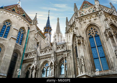 The impressive facade of Matthias Church in Budapest Hungary as the sun starts to set on the spires and tile roof - Stock Photo