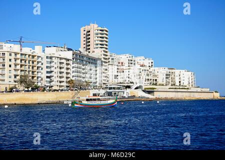 View along with waterfront with a tour boat in the foreground, Sliema, Malta, Europe. - Stock Photo