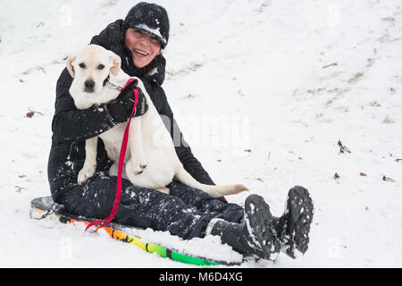 Windsor, UK. 2nd Mar, 2018. A puppy enjoys a ride on a toboggan on Snow Hill in Windsor Great Park. Credit: Mark - Stock Photo