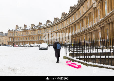 BATH, UK - MARCH 2, 2018 :  A woman drags a sled along the pavement in snowy conditions at the Circus, a Georgian - Stock Photo