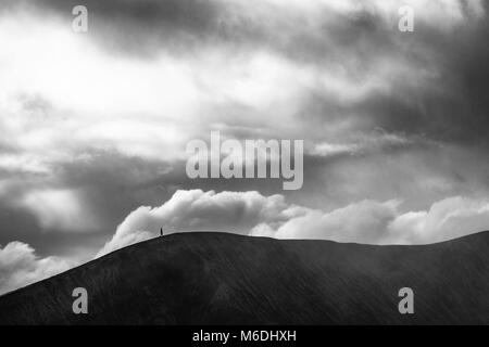 A black and white timeless capture of a person walking on the crater of massive Mount Bromo volcano under the heavy - Stock Photo