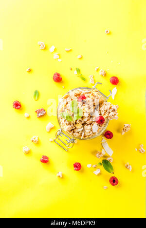 Healthy breakfast and snack concept, homemade granola with fresh raspberries in jar, on bright yellow background - Stock Photo