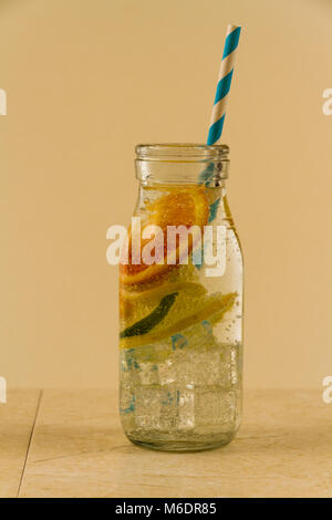 Children's sparkling water drink in bottle with straw. Slices of orange, lemon and lime. - Stock Photo