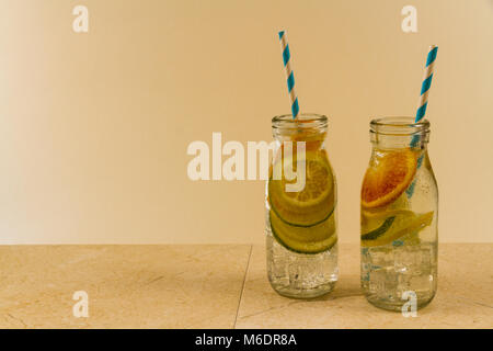 Children's sparkling water drinks in bottles with straw. Slices of orange, lemon and lime. Copy space on left. - Stock Photo