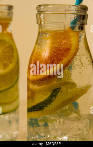 Children's sparkling water drinks in bottles with straw. Slices of orange, lemon and lime. - Stock Photo