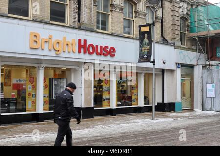 Man dressed in black walks past the Bright House weekly payment consumer goods store in Ipswich town centre. March - Stock Photo