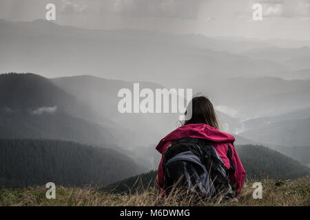 Young female hiker with backpack sits in grass on top of hill in ukrainian carpathians - Stock Photo