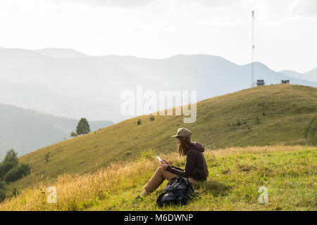 Hiker female uses portable tablet pc in mountains near cellphone tower - Stock Photo