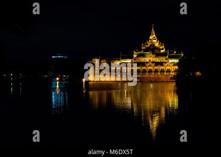 Karaweik Palace hall barge, lit up golden bright at night reflecting on Kandawgyi Lake, Yangon, Myanmar, Burma, - Stock Photo