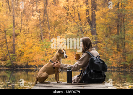 Girl and her pet staffordshire terrier hiking in the forest and have a rest at riverbank, female having big cup - Stock Photo