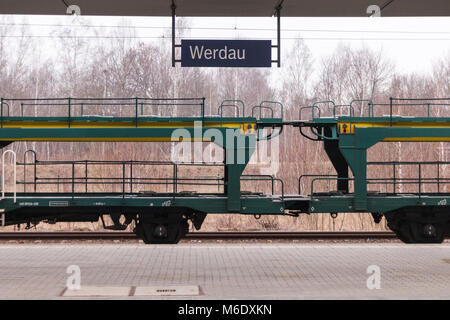 Werdau, Germany - March 2,2018: View of the platform in Werdau with the name plate of the station and a freight - Stock Photo
