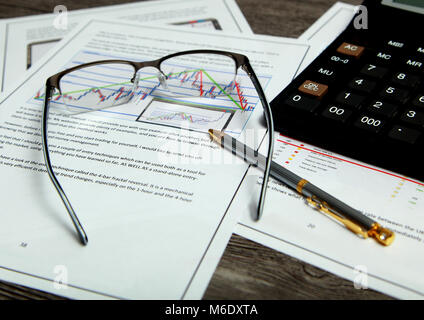 On the table with financial documents are calculator, pen and glasses. - Stock Photo