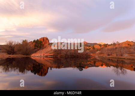 The early morning light casts a reflection on the calm water in Red Rock Canyon.  Colorado Springs, Colorado. - Stock Photo