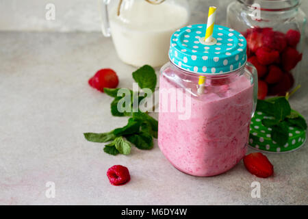 Mason jar mugs with fresh berry cocktails and ingredients for cooking smoothies (strawberries, raspberries, milk) - Stock Photo