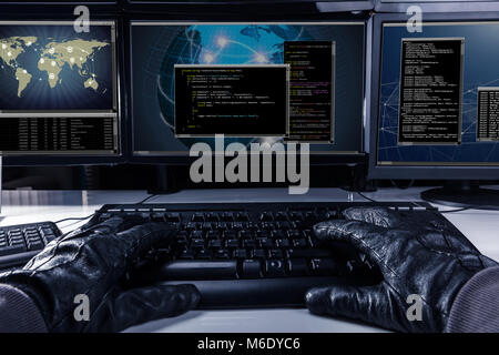 Hacker Wearing Gloves Typing Code On Keyboard In Front Of Multiple Computers - Stock Photo