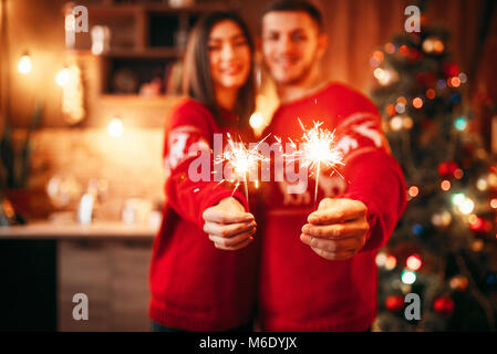 Love couple holds sparklers in hands, christmas romantic celebration. Man and woman celebrate xmas together - Stock Photo