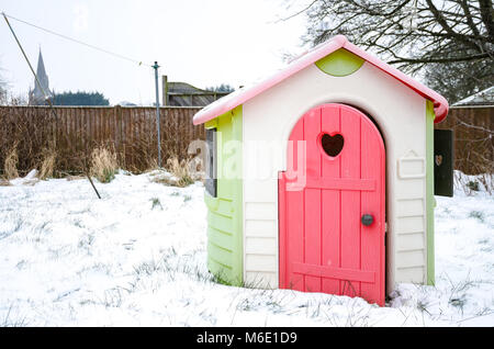 A child's toy house pictured in the back garden on a snowy day. - Stock Photo