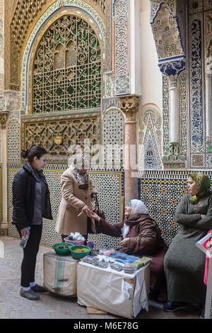 Shop of incense and henna, customers and saleswoman, in background facade of Zaouia (tomb) of Moulay Idriss II, - Stock Photo