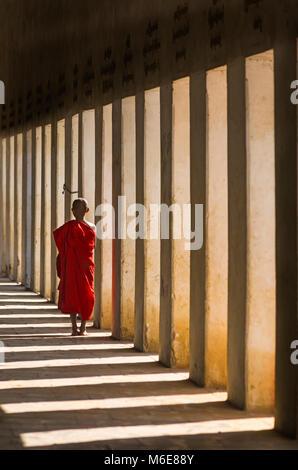 Novice Buddhist monk walking along eastern stair way of Shwezigon Pagoda, Nyaung U, Bagan, Myanmar (Burma), Asia - Stock Photo