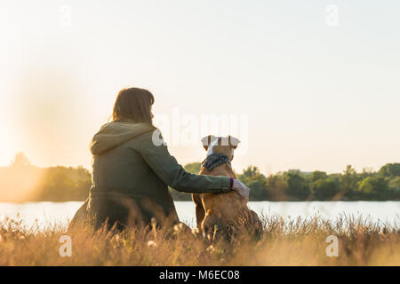 Dog owner and her pet sit at riverbank at sunset - Stock Photo