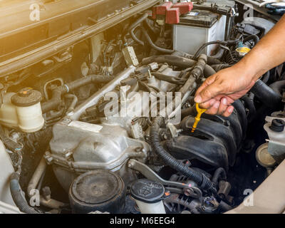 Hand of car mechanic working in auto repair service. He have fix old car engine streaked with dust and oil stains - Stock Photo