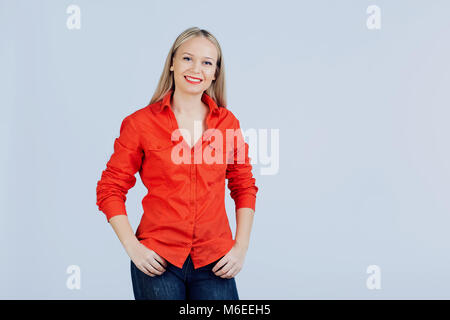 Young blonde woman in casual clothing with positive emotion on a gray background. - Stock Photo