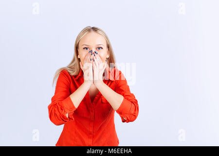 Blonde woman in casual clothes with a surprised emotion on a gray background. - Stock Photo