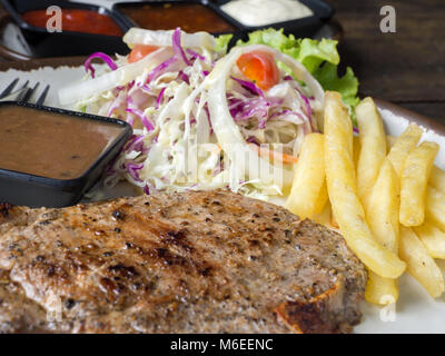 close up of T-bone steak with salt and pepper, golden french fries and green vegetables. on white plate, Fork and - Stock Photo