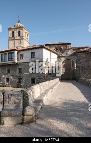 Puerta del Portazgo with 14th century Colegiata de San Miguel in background, Aguilar de Campoo; Palencia; Spain - Stock Photo
