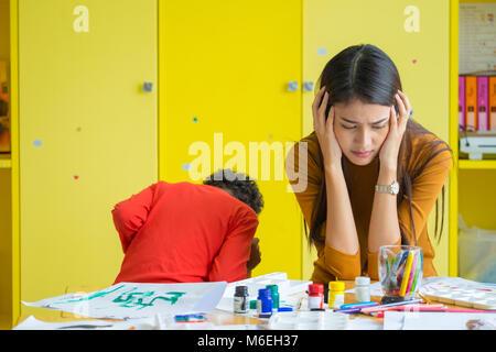Teacher get headache with two naughty kids in classroom at kindergarten school - Stock Photo