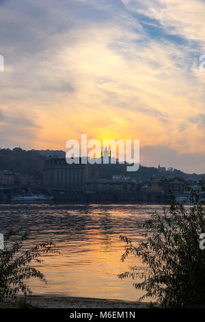View of sunset over Saint Andrew's church in Kyiv, Ukraine. Dnipro river on the foreground - Stock Photo