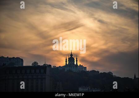 Sunset over Saint Andrew's church in Kyiv, Ukraine. Dramatic skyline view - Stock Photo