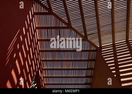 The framed roof of the Tamarin Bay Hotel casts interesting shadows on the angled ochre walls upon which it sits. - Stock Photo