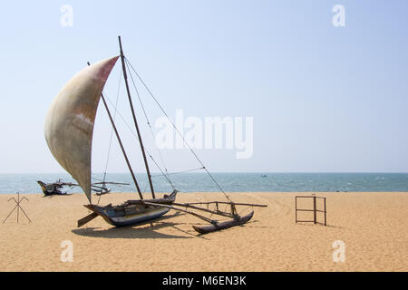Oruwa fishing catamaran or a traditional Sri Lankan fishing boat in shape of an outrigger canoe on an empty beach - Stock Photo