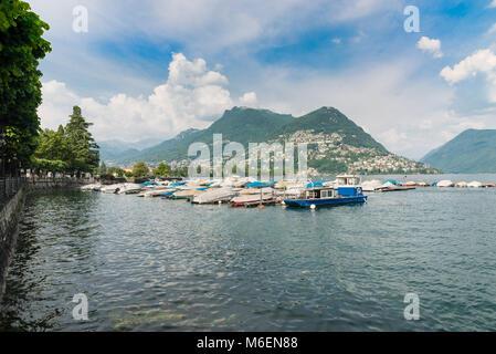 Lugano city, lake Lugano, Switzerland. Gulf of Lugano, Lugano lakeside promenade and Bre mountain on a beautiful - Stock Photo
