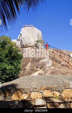 Buddhist monk climbing the Mihintale peak in Sri Lanka, not far from the Anuradhapura ancient town. - Stock Photo
