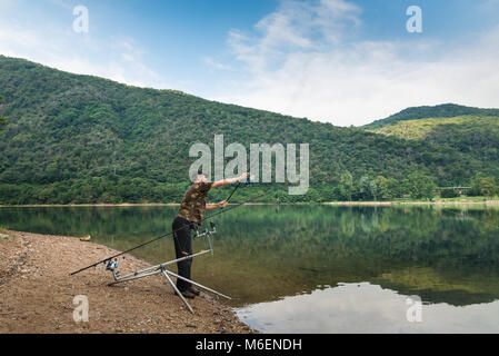 Fishing adventures, carp fishing. Angler with camouflage t-shirt and a fishing rod in his hand, is casting the bait - Stock Photo