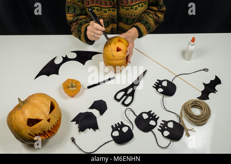 Making halloween decorations including paper figures, skulls and cutting scary faces of pumpkins - Stock Photo