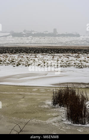 Frozen river and snow covered fields of Hadleigh Marsh with Hadleigh Castle and Country Park beyond. Beast from - Stock Photo